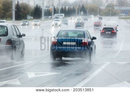 Blurred View Of City Cars Moving Along Wet Road During Rainy Day