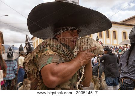 June 24 2017 Cotacachi Ecuador: indigenous kichwa man blowing into a conch shell horn while dancing in the street at the Inti Raymi parade at summer solstice