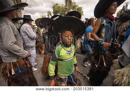 June 24 2017 Cotacachi Ecuador: indigenous kichwa boy wearing chaps dancing in the crowd at the Inti Raymi parade at summer solstice