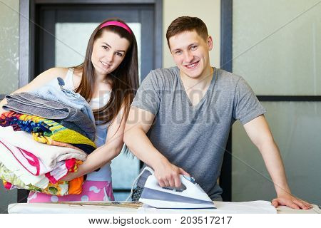 A Young Man Irons Clothes.the Young Man Doing House Chores.the Guy In Home Clothes Irons.a Girl Carr