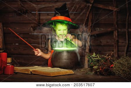 Halloween. little witch child cooking potion in the cauldron with spell book