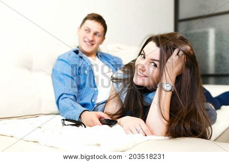 Beautiful Girl And A Young Man Sitting On The Couch And Watch Tv.young People Relax On The Couch.you