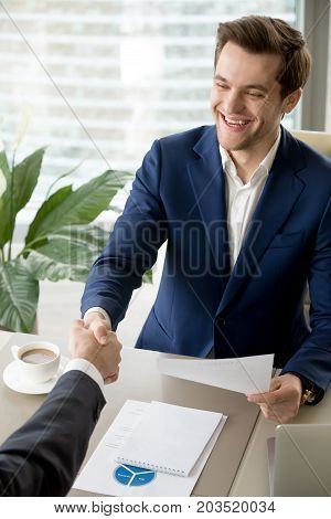 Happy smiling businessman holding contract and handshaking with business partner in office. Company leader enjoying successful negotiation, satisfied with profitable deal, accepting terms of agreement