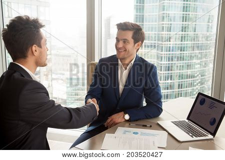 Smiling CEO in stylish blue business suit handshaking with partner while sitting at desk with laptop and documents. Boss welcoming company new employee. Financial advisor meeting with client in office