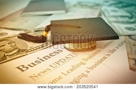 Graduation cap on a letter book Business News update Concept of graduate education MBA abroad in university requires a lot foreign currency Dollars to bring success in famous institution.