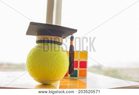 Graduation cap Put on Ball and Rubik's Cube Tennis is a racket sport can be played individually against single opponent Sports competition success concept
