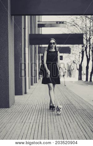 young fashion woman in dark dress, walking her little dog in the street. white and black photo