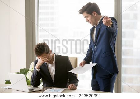 Boss criticizing frustrated male employee because of mistakes in report, having claims to work, threatening with dismissal from work and points on door. Stressed office worker listening mad manager