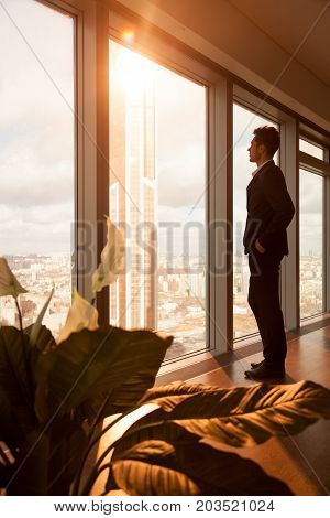 Successful businessman standing in modern office interior looking through large window at sun and urban landscape with skyscraper. New luxury apartment owner enjoying beautiful city view at morning