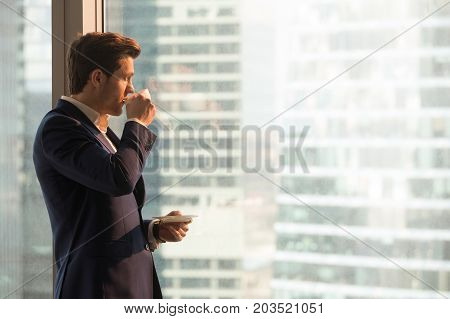 Thoughtful man looking through window and drinking morning tea in office. Successful company leader enjoying cup of coffee after work day, taking break to think about important decision. Copy space