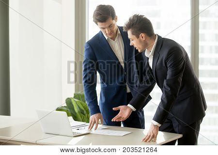 Businessman conducting presentation with business documents to convince investor to finance project. Realtor explaining benefits of estate object when showing drawings or construction plan to client