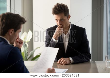 Nervous male job candidate looking with worriment on human resources generalist reading his resume during interview in company office. Millennial man trying to find job, giving application for vacancy