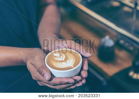 Man hands holding fresh coffee or latte art in white cup at coffee shop and restaurant bar or pub.