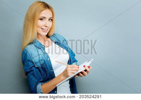 Make some notes. Delighted blonde keeping smile on her face and writing something while standing in semi position over grey background