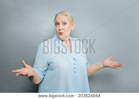 Emotional pensioner. Beautiful pensioner keeping eyes wide opened and raising hands while looking straight at camera