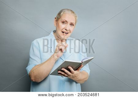 Want to make notes. Cheerful senior female raising eyebrows and holding notebook while looking straight at camera