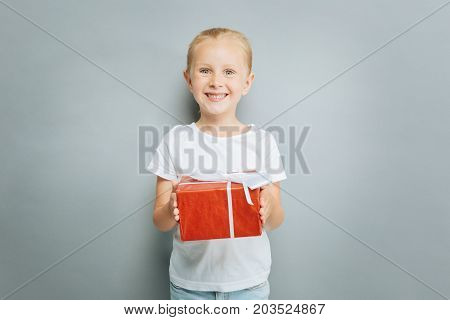 Take it. Delighted blonde keeping smile on her face and looking straight at camera while demonstrating red box