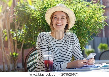 Outdoor Photo Of Pretty European Girl Dressed Casually And Trendy As She Spends Leisure Time In Cafe