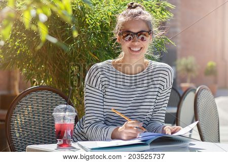 Horizontal Photo Of Beautiful Caucasian Woman Looking Straight At Camera Through Sunglasses And Smil
