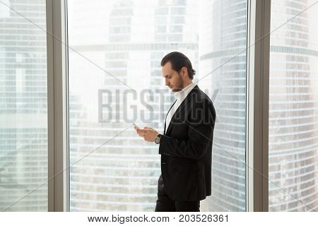 Young handsome businessman in expensive dress suit in modern office next to the window is looking at his cellphone with serious expression. Urgent message received or looking for information concept.