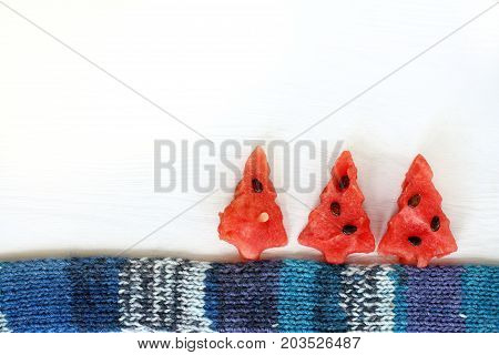 fictional installation of sweet Christmas trees and a warm scarf on a light wooden surface / winter in a watermelon forest