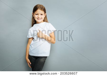 I am model. Glad child keeping smile on her face and posing like a model while looking straight at camera