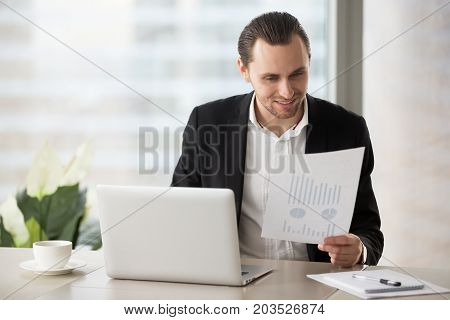 Young cheerful business man sitting in modern office in front of laptop with happy smile, holding financial report document, pleased with successful stock investment profit. Finance success concept.