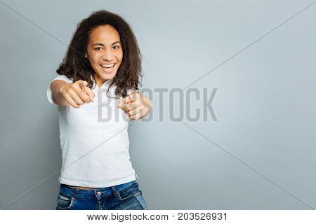 Pointing at you. Amazing foreign girl expressing positivity and looking straight at camera while standing over grey background