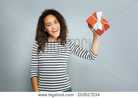 Just have a look. Delighted woman keeping smile on face and holding red box while looking at camera