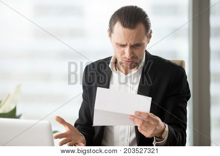 Frustrated young businessman in suit looking at confusing letter in modern office setting. Unexpected high bill, unpaid debt, failing financial report, tax delinquency, breach of contract concept. poster