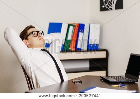 Tired Young Handsome Businessman In Glasses Sits In The Office At His Workplace At The End Of The Da