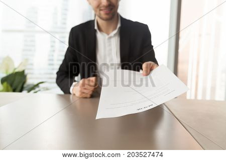 Smiling job applicant in suit handing over resume to recruiter during interview. Modern office setting. Recruitment manager giving resume back to candidate. Human resources, hiring, interview concept.