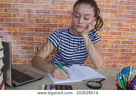 Young Girl studying on desk at home. Thoughts education creativity concept. young attractive student Girl studying lessons