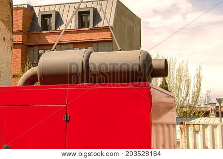 Stationary diesel electric generator with an exhaust pipe from above near old houses. Close-up fragment. Outdoors.