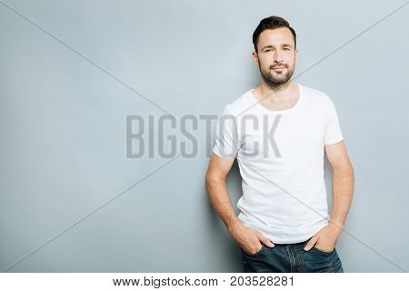 Cool guy. Delighted bearded brunette man pressing lips while posing on camera and standing over grey background