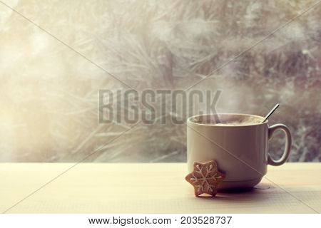 foamy steaming coffee with milk in a white mug is on the table opposite the frozen window / warming drink for winter morning
