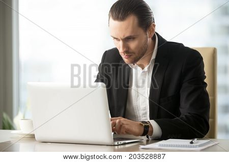 Serious young handsome busy businessman working on laptop at desk at workplace in office. Researching stock investment market, communicating with business partners, taking care of financial inquiries.