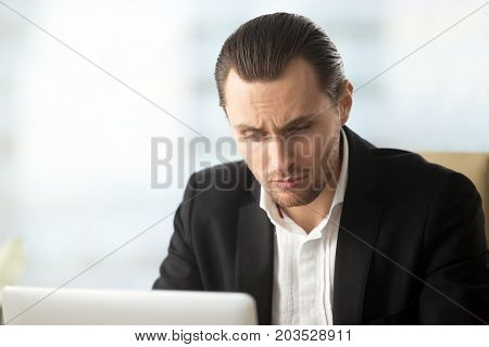 Perplexed or puzzled handsome businessman looking at laptop screen. Confused project manager double checking important financial information, results not making sense. Difficult work task concept.
