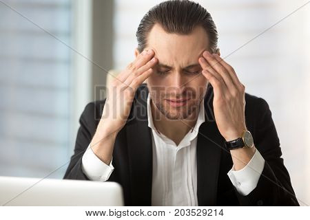 Exhausted businessman having headache after long working hours. Project manager rubbing temples with hands trying to relieve stress pain. Heavy workload, stressful day, unpleasant difficult work task.