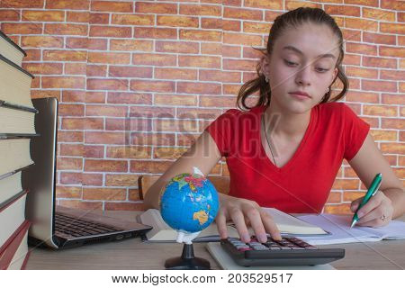 Young girl student sitting between books and calculate. Student Young Girl with bills and calculator in the room at home. Thoughts education creativity concept
