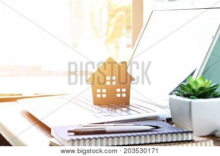 Business, finance, savings, property ladder or mortgage loan concept : Wood house model on computer laptop