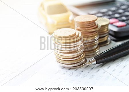 Business, finance, saving money, banking or car loan concept : Miniature car model, coins stack, calculator and saving account book or financial statement on office desk table