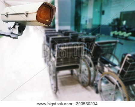 CCTV security indoor camera system operating with blurred image of empty wheelchair for patient in hospital surveillance security safety technology concept