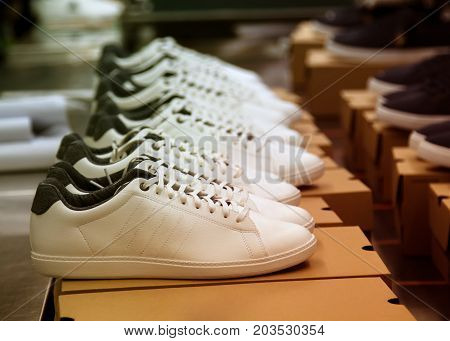 white leather shoes flowing on production line conveyor in footwear factory