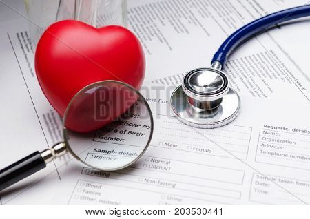 stethoscope magnifying glass red heart and patient information form on desk heart attack heart disease medical diagnosis medical report record and history patient concept selective soft focus