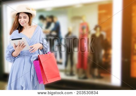 cheerful young asian woman watching special offer in mobile tablet and holding shopping bags while standing at clothes shop in department store shopping mall online payment shopping online concept