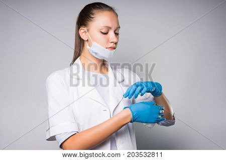 A cute girl doctor wearing a mask on her face, putting on gloves. Pensive woman looking down