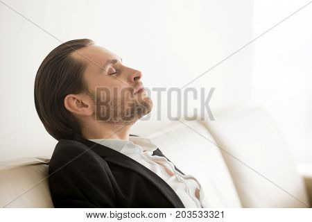 Calm businessman resting or meditating with eyes closed, using breathing techniques. CEO taking care of his health during break. Reducing discomfort at workplace, staying in focus, relieving stress.