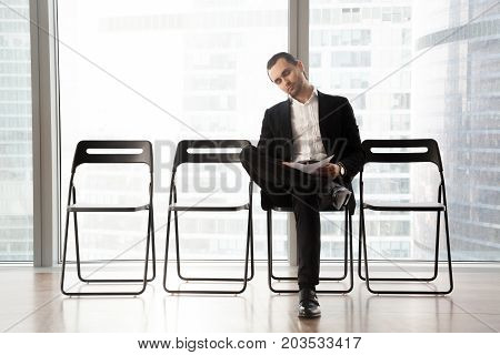 Relaxed businessman in formal suit fell asleep while waiting for interview with HR or business meeting to start. Job candidate or entrepreneur holds resume patiently awaits his turn. Patient applicant