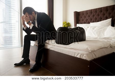 Frustrated young man in formal suit sitting on bed besides luggage bag. Businessman thinking about problems in business or at home, not feeling well, lost job, relationships or work related stress.